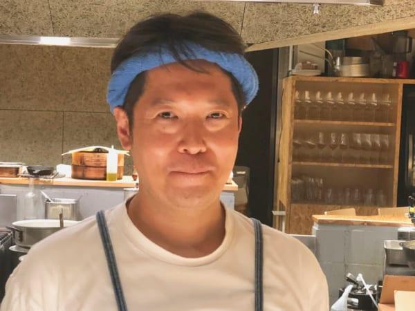 Tシャツにエプロン、ねじり鉢巻で炭と向き合うカッシーさんこと樫村シェフ。「写真、撮られ慣れていないんです」って顔が固まってますよ