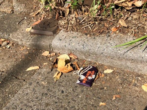 都内の路上にて発見した「成田山調布不動尊」のお守り。枯れ葉と一緒で哀愁3割増し!(写真/ダーシマ)