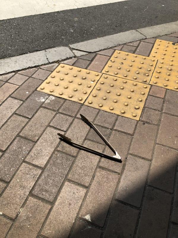 都内の路上にて発見したトング。焼肉店で使い、手にもったまま店を出てしまった、うっかりさんがいたのだろうか……。(写真/ダーシマ)