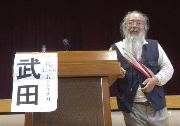 2017年、小学校の体育館で開いた個人演説会で演説する武田完兵候補。演説、演奏、質疑応答を重ねる。耳が遠いため、聴衆が候補者に選挙用のメガホンを使って質問するシステムだった。(撮影/畠山理仁)