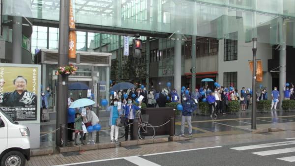 新田氏の演説を待ち構える支援者。青い風船や「新田」と書かれた青い札を持ち盛り上げる。(撮影/畠山理仁)