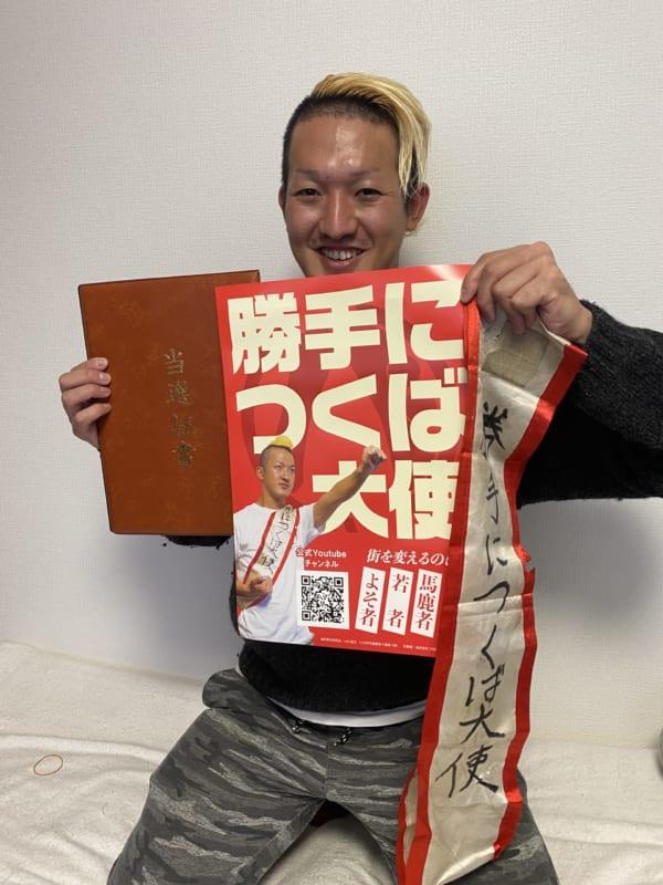 金髪モヒカンの「勝手につくば大使」。文字が蓄光インクで光るポスタービラと「勝手につくば大使」タスキ、そして当選証書。(撮影/畠山理仁)