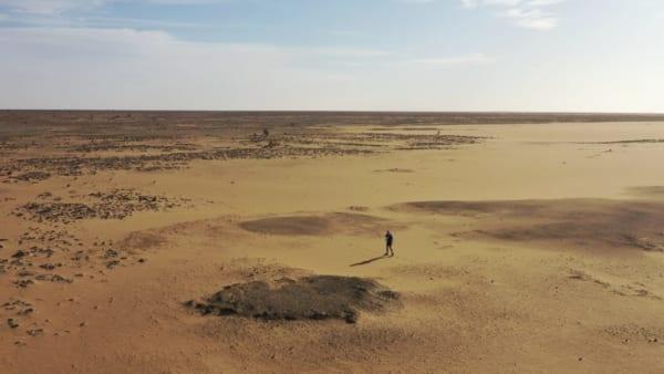 見渡す限り何もないサハラ砂漠。写真中央で小さく映るのが、この地で1000キロを走破した北田雄夫さん。